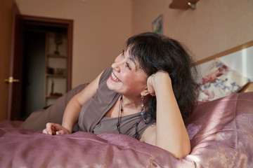 Nice middle-aged woman in the bed room. Lady at home