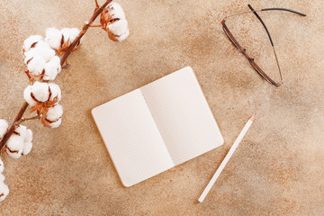 Open notebook with white pencil on beige background. Flat lay, top view, mock up.
