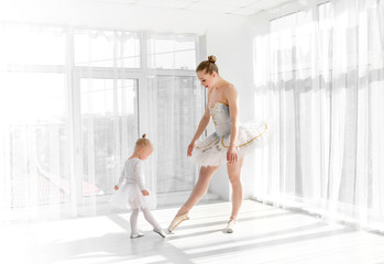Young gorgeous ballerina with her little daughter dancing in studio