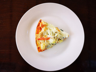 piece of pizza on white dish with dark brown table background. copyspace.