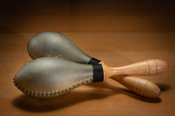 A pair of rawhide maracas lying on a wooden table