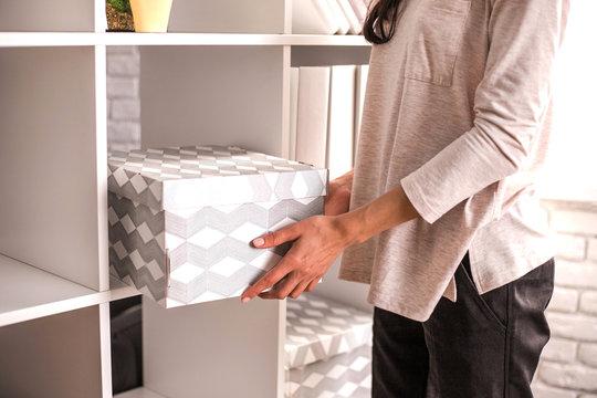 Woman put a cardboard box on shelf.