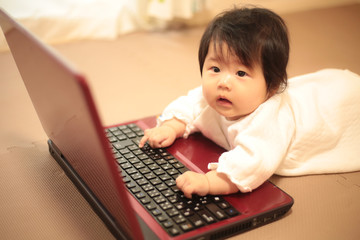 ノートパソコンに触れる赤ちゃん