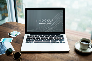 Laptop on a wooden table with a screen mockup