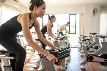 select focus of hand, burry background Young beautiful woman and man exercising  by riding a bicycle in a gym and sweating - Image