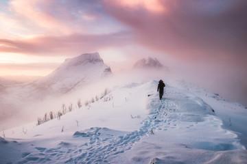 Man mountaineer walking with snow footprint on snow peak ridge in blizzard