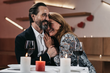 Happy man and woman are sitting in a restaurant. Woman leaned against a man