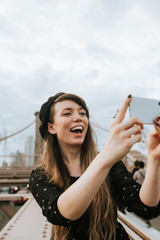 Cheerful woman taking a selfie with The Brooklyn Bridge, USA