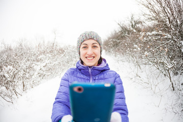 A woman makes a photo on a mobile phone in the winter forest.