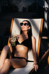 Side view of beautiful young woman in sunglasses and swimsuit holds a glass with cocktail, looking at the sea, dreaming, while resting on luxury sunbed. Summertime.