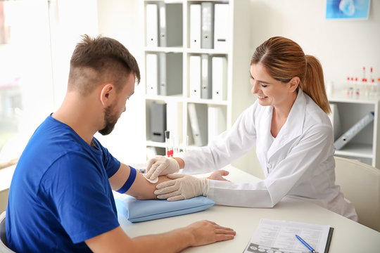 Female doctor preparing patient for blood draw in clinic