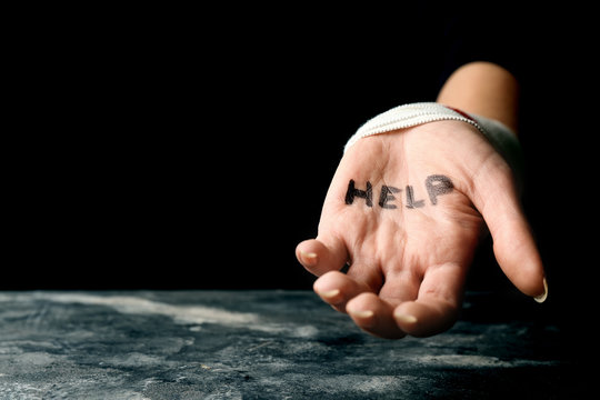 Woman with wrist bandage and word help written on her palm. Suicide awareness concept