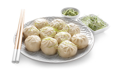 Plate with tasty Chinese dumplings, wasabi and sprouts on white background