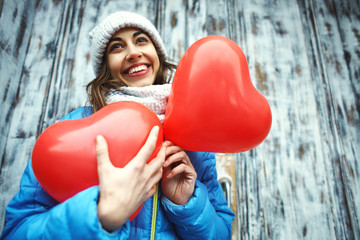 happy young woman in warm winter clothes, knitted cap and scarf is standing outdoors with a heart shaped red balloons