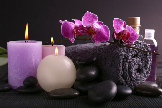 Beautiful spa composition with candles, stones and bath towel on dark table