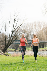 Senior woman with daughter running along the river away from the viewer