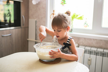 Girl child helps in kitchen,mixes dough in bowl