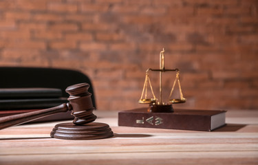 Judge gavel with law book and scales of justice on table