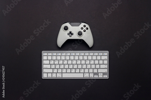 White gamepad and keyboard on a black background  Tactics of the