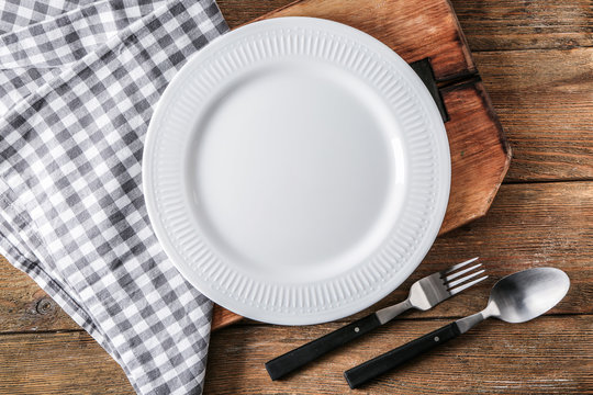 Empty ceramic plate with cutlery, napkin and board on wooden background