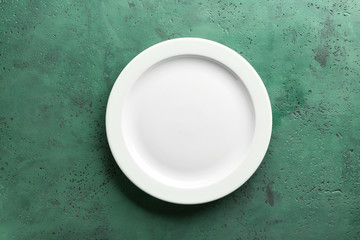 Clean empty plate on color background