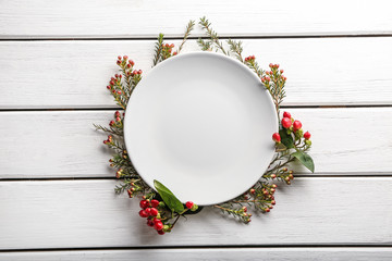 Clean empty plate and floral decor on white wooden background