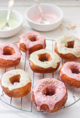 Homemade donuts decorated with colored icing and colored sugar on a light background.