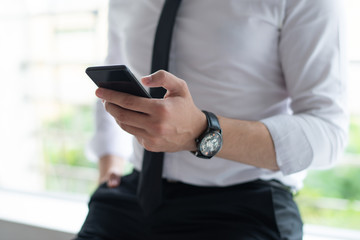 Closeup of business man texting on smartphone and leaning on sill. Person wearing tie and holding smartphone. Business and communication concept. Cropped view.