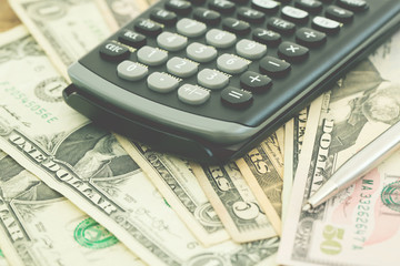 calculator on the background of Money dollar banknotes. soft focus.