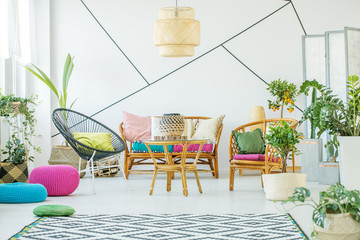 Urban jungle and patterned carpet on white wooden floor in chic living room interior with rattan sofa, armchairs and coffee table