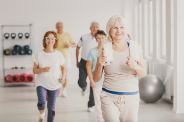Smiling senior fitness instruct exercising with group of active seniors