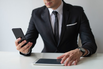Business leader sending data from smartphone to tablet. Closeup of businessman using smartphone and tablet at his workplace. Wireless data exchange concept