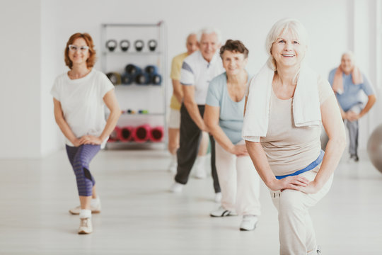 Smiling senior woman exercising with group of active seniors in fitness center