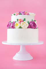 Two-tiered white wedding cake decorated with color cream flowers on a pink background.