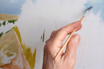 hand of an elderly person paints a picture with a brush