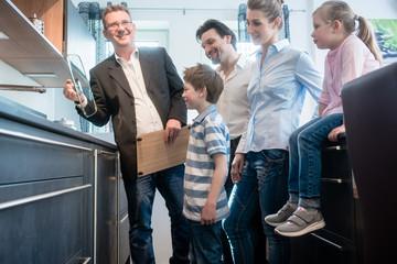 Berater zeigt einer Familie die Details der neuen Küche