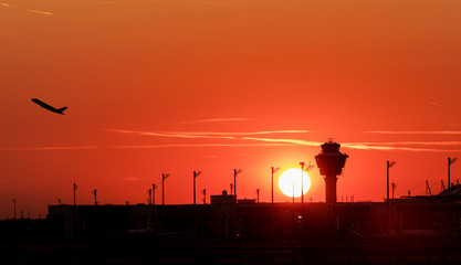 Airport control tower and airplane during sunset.