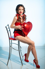 Girl in red shorts, with a red inflatable heart