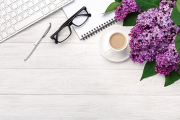 Office desktop with a bouquet of lilacs, coffee cup, keyboard, notebook and pen on white boards