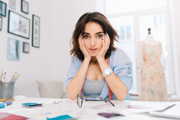 A pretty brunette girl is sitting at the table in the workshop studio. She wears blue shirt and white watch. She supports her face with hands and is looking to camera.