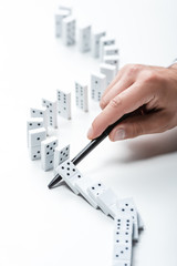 partial view of man preventing dominoes from falling with pen on white background