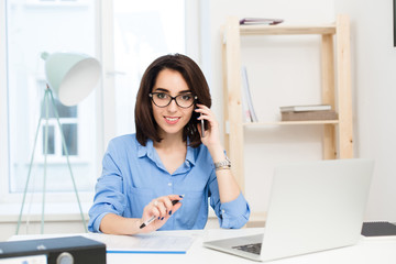 A pretty young girl is sitting at the table in office. She has blue shirt and black glasses. She is speaking on phone and smiling to the camera.