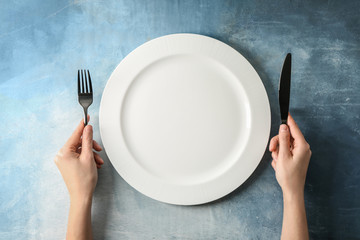 Female hands with cutlery and empty plate on color background Wall mural