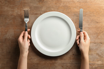 Female hands with cutlery and empty plate on wooden background Wall mural