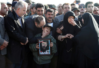 A boy holds a picture of a man who died in a Boeing 707 military cargo plane crash, during a funeral at Mehrabad airport in Tehran