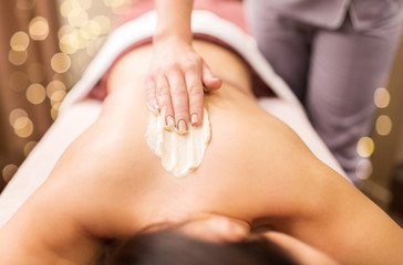 people, beauty, healthy lifestyle and relaxation concept - beautiful young woman lying and having back massage with cream at spa