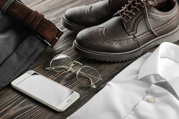 Stylish male clothes and accessories on wooden background