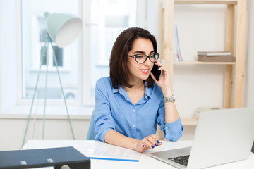 A young brunette girl is working at the table in office. She wears blue shirt and black glasses. She is speaking on phone.