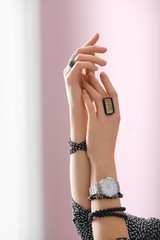 Hands of beautiful young woman with stylish bijouterie on color background
