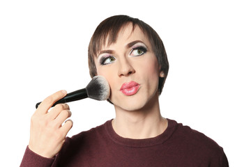 Portrait of transgender man applying makeup onto his face against white background